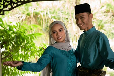 front view of malay couple standing in front of house waiting for visitors