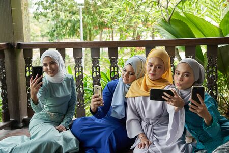 women with traditional clothing using smart phone during ramadan festival celebration