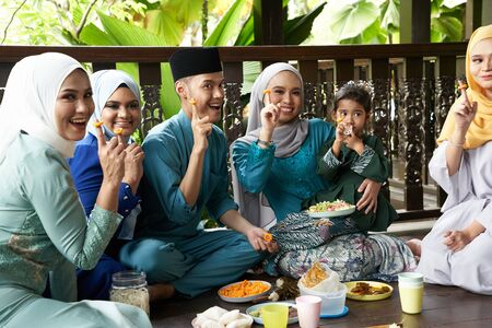 group of malay family breaking the fast together they showing the cheese ring