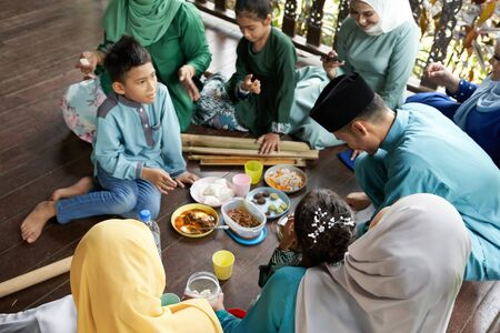 focus on the foreground group of malay family breaking the fast together
