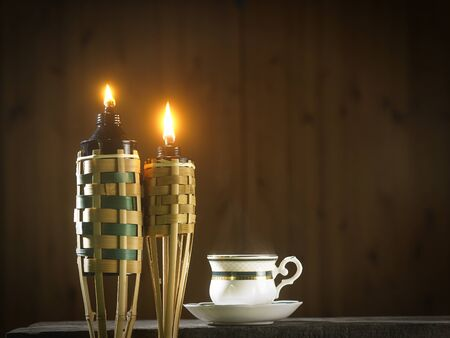 bamboo torch or pelita with cup of hot tea
