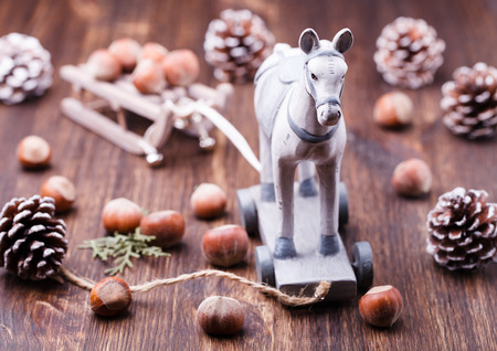 horse sleigh: Christmas and new year toy, horse sleigh, hazelnuts and cones. The decoration on holiday background greeting card.