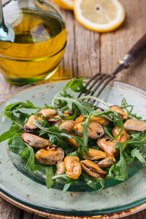 Salad with mussels and arugula on a glass plate with olive oil and lemon.selective focus