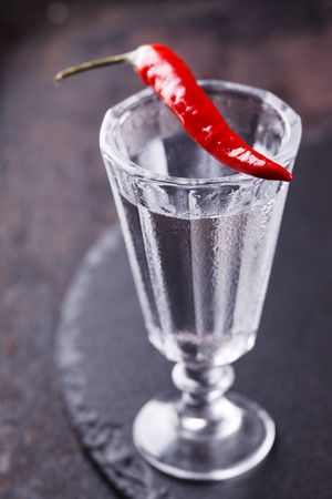 sober: Shot of vodka with chili pepper on a black background
