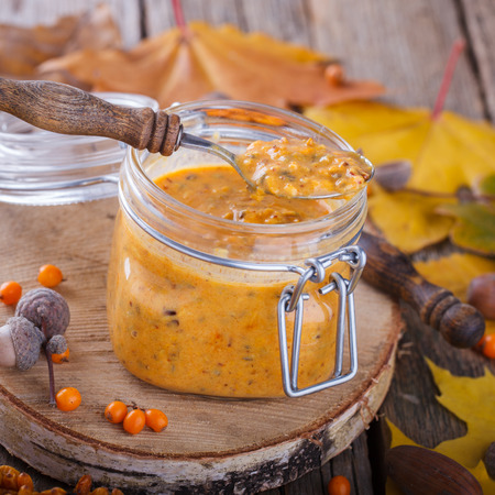 argousier: Twisted sea-buckthorn berries with sugar in a glass jar,jam useful.Autumn still life.selective focus.