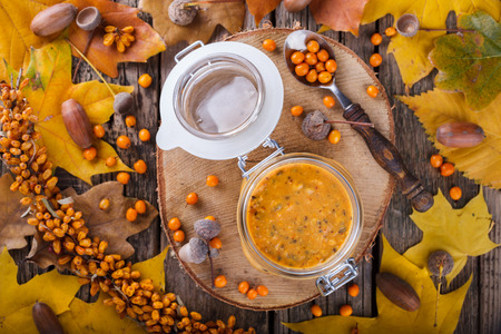 seabuckthorn: Twisted sea-buckthorn berries with sugar in a glass jar,jam useful.Autumn still life.selective focus.