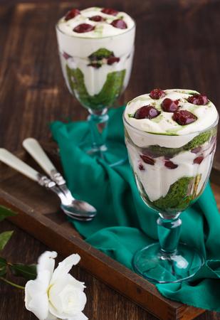 rum cake: Tiramisu in a glass of tea match and cherry Stock Photo