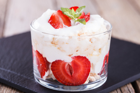 mess: Eton Mess - Strawberries with whipped cream and meringue in a glass beaker. Classic British summer dessert.selective focus