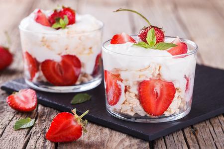 postres: Eton Mess - Fresas con crema batida y merengue en un vaso de vidrio. Clásico enfoque dessert.selective verano británico