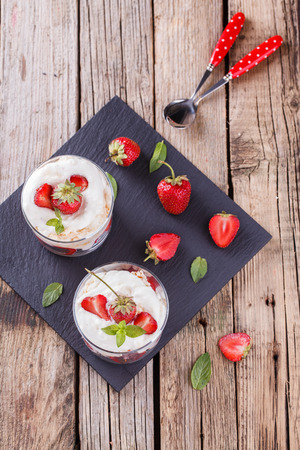 eton mess: Eton Mess - Strawberries with whipped cream and meringue in a glass beaker. Classic British summer dessert.selective focus