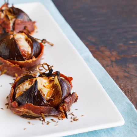 Baked figs with cheese wrapped in bacon.selective focus