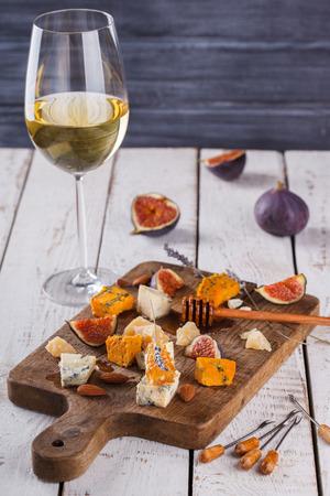 queso de cabra: Uva, queso, higos y miel con unos vasos de vino tinto y blanco sobre una tabla de madera. Enfoque Board.selective Queso