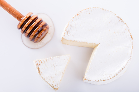 ingram: Brie cheese on with a white background with fresh Ingram and honey.selective focus.