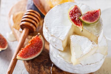 queso blanco: queso brie en una tabla de madera con higos frescos y enfoque honey.selective. Foto de archivo