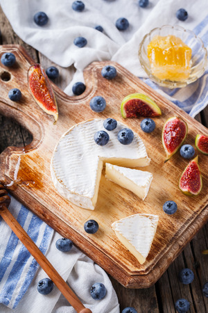 ingram: Brie cheese,Camembert with Ingram,blueberries and honey on a wooden Board.selective focus Stock Photo