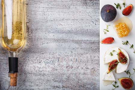 치즈 보드, 전채. 브리 치즈, 카망베르, 화이트 와인 한 병, 무화과, 꿀, 백리향 및 화이트 와인. 공간 복사. 선택 집중