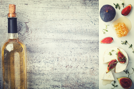 cheese platter: Cheese Board,appetizer.Brie cheese,Camembert,bottle of white wine,figs,honey and thyme and white wine.Copy space. Toned image. Vintage style.selective focus
