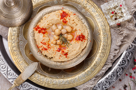 lebanese food: Hummus, chickpea dip, with rosemary, smoked paprika and olive oil in a metal bowl .selective focus Stock Photo