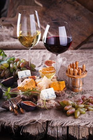 Grape, cheese, figs and honey with a glasses of red and white wine.Cheese Board.selective focus