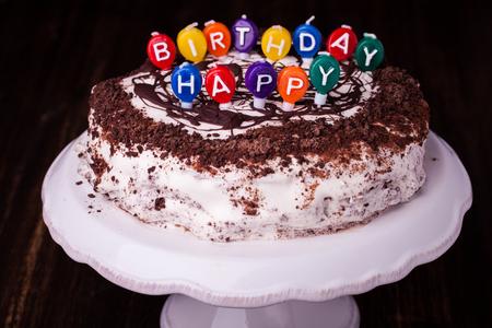 Un gâteau et ses bougies qui lisent Joyeux anniversaire.