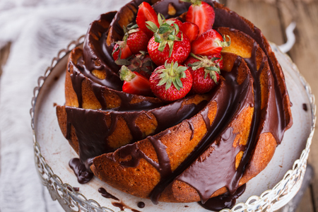 cream cake: Cake with strawberries and chocolate glaze on the base.selective focus