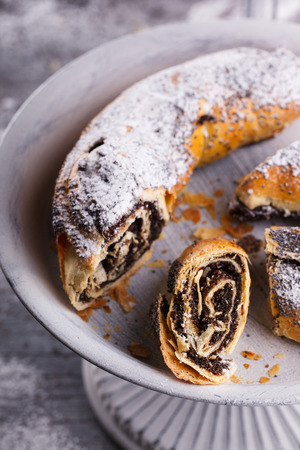 poppy seeds: Strudel with poppy seeds on a vintage stand.selective focus. Stock Photo