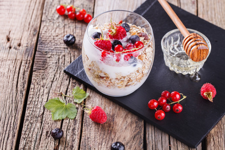 Breakfast with muesli, yogurt,honey and fresh berries in a glass on a wooden background. selective focus