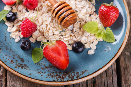 hone: Muesli with fresh berries and hone, on the blue plates Healthy Breakfast.selective focus Stock Photo