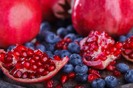 Juicy pomegranates,whole and broken and blueberries on wooden background.selective focus.