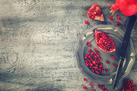 pomegranate: Juicy pomegranates,whole and broken vintagey on a metal plate.Toned image. Vintage style.Copy space.selective focus.
