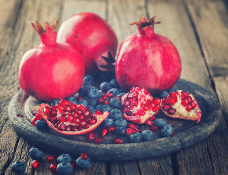 Juicy pomegranates,whole and broken and blueberries on wooden background.Toned image. Vintage style.Copy space. selective focus.