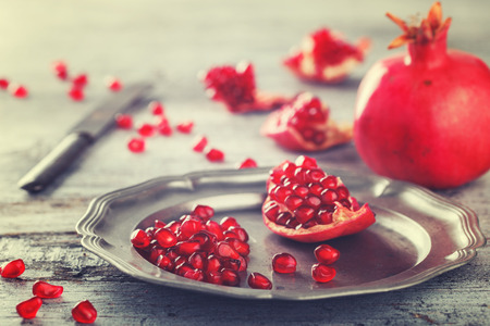 pomegranate: Juicy pomegranates,whole and broken vintage on a metal plate.Toned image. Vintage styleselective focus.