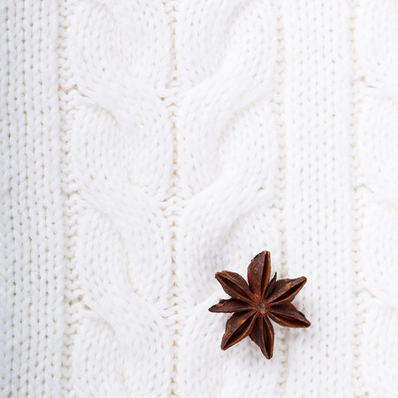 cable knit: Christmas spices,anise  a knitted white background,texture of natural fibers. Stock Photo