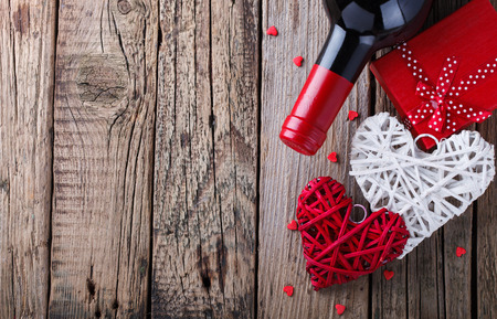 Gift , the heart and the bottle of red wine for a romantic holiday Valentine's day on vintage wooden background.Copy space.selective focus. 写真素材