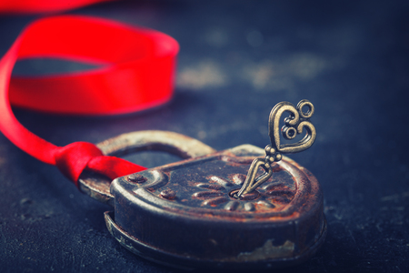 closed ribbon: Padlock with key and a red ribbon ,the symbol of love.The background to the Valentines day.Toned image.Vintage style.selective focus. Stock Photo