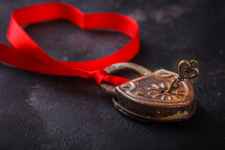 Padlock with key and a red ribbon ,the symbol of love.The background to the Valentines day.selective focus.