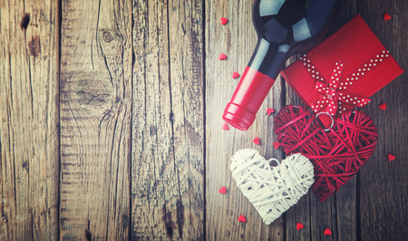 Gift , the heart and the bottle of red wine for a romantic holiday Valentine's day on vintage wooden background.Toned image.Vintage style.Copy space.selective focus.