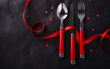 Romantic Valentines Day celebration, a set of silverware on a dark background,decorated with red ribbon and hearts.selective focus