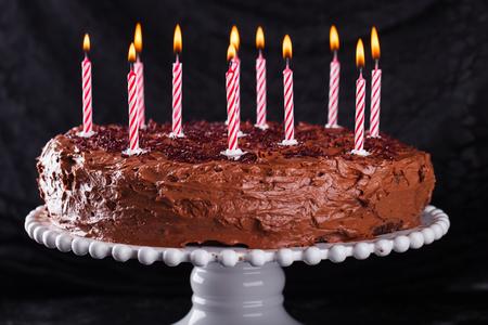 candela: Torta al cioccolato su uno sfondo scuro, di compleanno, con messa a fuoco candles.selective Archivio Fotografico