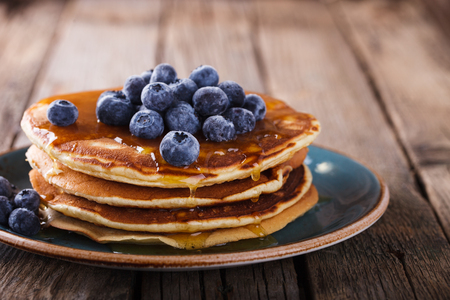 Pancake folded stack of with liquid honey and fresh blueberries on wooden background.