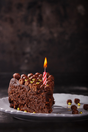 Piece of chocolate cake with candle on a dark background.selective focus.