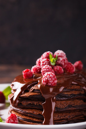 Chocolate pancake with chocolate glaze,raspberries and mint.selective focus Imagens