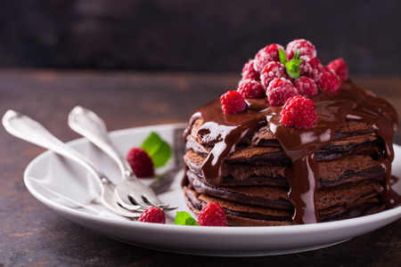 Chocolate pancake with chocolate glaze,raspberries and mint.selective focus Stock Photo