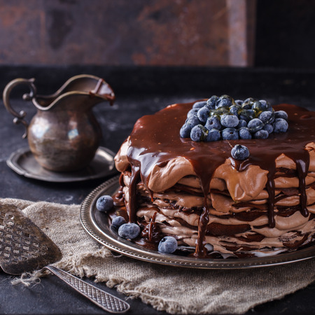 cakes and pastries: Chocolate cake from chocolate pancakes with icing, with blueberries.Vintage style.selective focus. Stock Photo