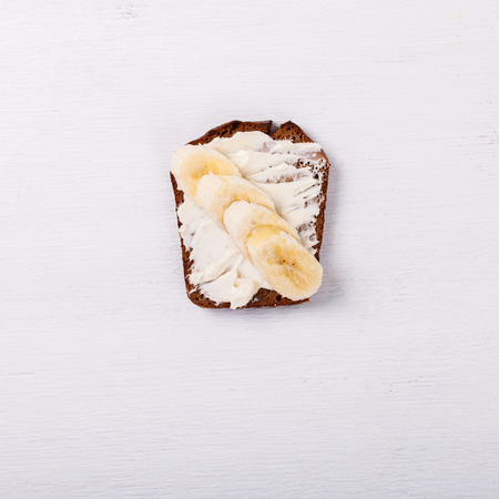 Sweet sandwich with cream-cheese and banana over a white background . Top view. healthy breakfast.Copy space.selective focus.