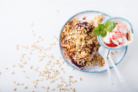 to crumble: Crumble plums with ice cream. Stock Photo