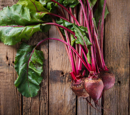 haulm: Young,fresh beets with tops on old wooden background. Vintage style. selective focus. Stock Photo