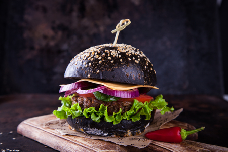 Beef burger with a black bun,with chilli,with lettuce and mayonnaise and ketchup served on pieces of brown paper , on a dark background.selective focus