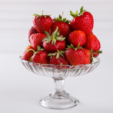 Fresh strawberries in a glass vase on a white background. Vegetarian and healthily cooking concept.selective focus.