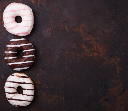 glazes: Donuts in colored glazes on a dark background.Pastries,dessertCopy space.selective focus. Stock Photo